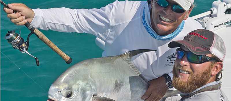 Permit fish caught by angler poses with fishing guide